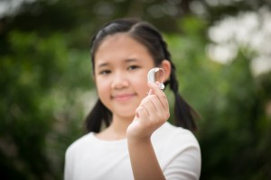 12.1 Asian girl holding hearing aid